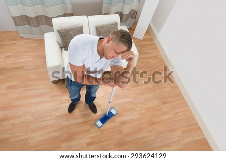 Tired Young Man Standing With Mop At Home