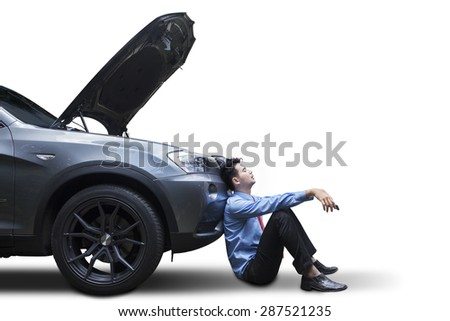 Tired young man waiting a help while sitting near the broken car, isolated on white - stock photo