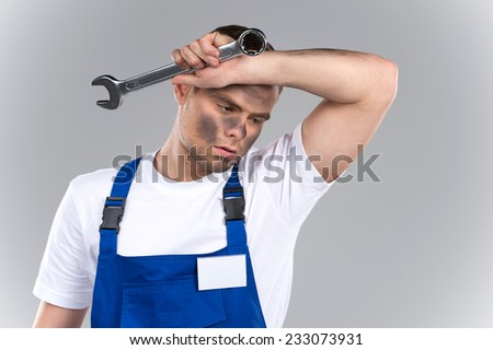 Tired young mechanic in blue overall on blue background. closeup of dirty man holding wrench and wiping sweat of fore head - stock photo