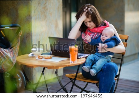 Tired young mother working oh her laptop and holding 4-month son - stock photo