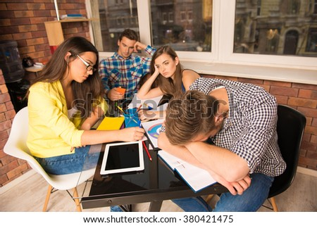 Tired young people working together in office - stock photo