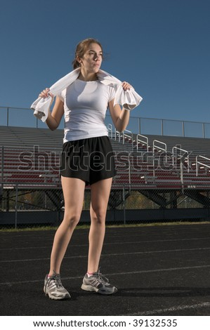 Tired young thin woman relaxing after exercising outdoors, with a towel around her neck - stock photo
