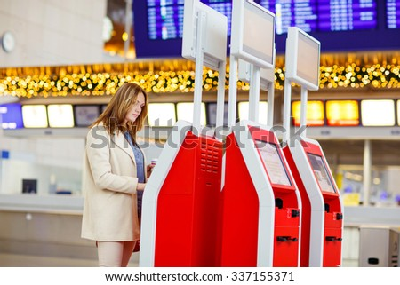 Tired young woman at international airport checking in on electronic terminal waiting for her flight. Upset passenger. Canceled flight due to pilot strike. - stock photo