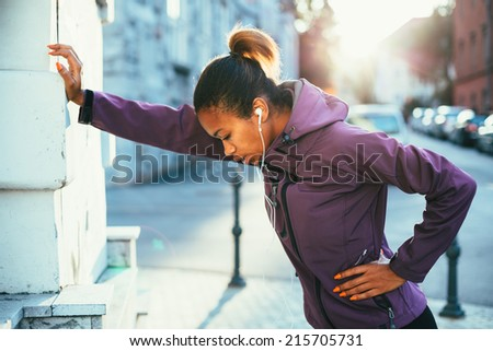 Tired young woman catching her breath after a long run - stock photo