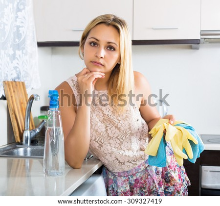 Tired young woman cleaning furniture in kitchen