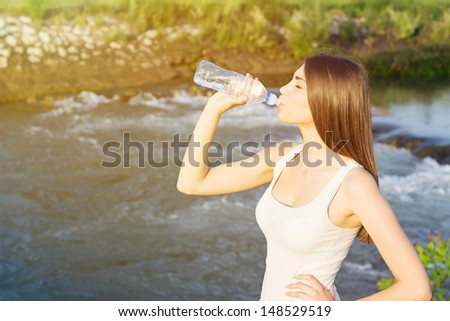 Tired young woman drinking water after running by the river - stock photo