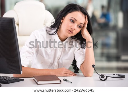 Tired young woman is sitting at the table at work in a call center. - stock photo