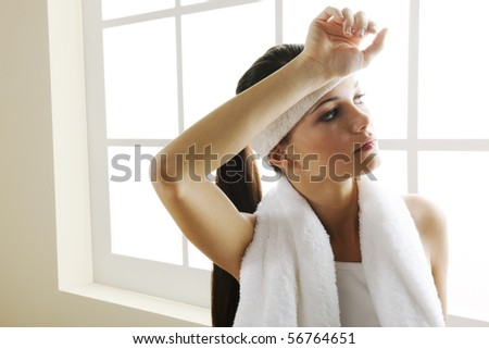 Tired young woman resting after exercising - stock photo