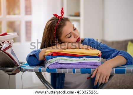 Tired young woman sleeping on the ironed laundry at home - stock photo