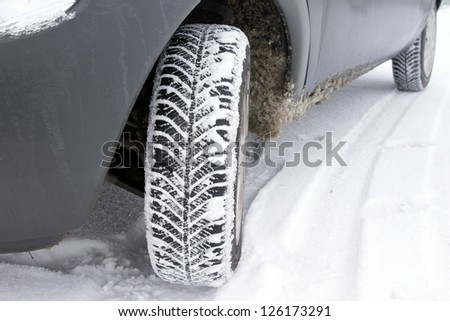 tires on the road are covered with snow on a winter day - stock photo