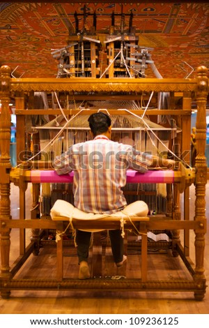 TIRUNELVELI, INDIA - DECEMBER 9: An unidentified Indian man makes a traditional sari to demonstrate a handloom on December 9, 2009 in Tirunelveli, India - stock photo