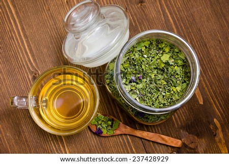 Tisane mauve inside cup on wooden table top view - stock photo