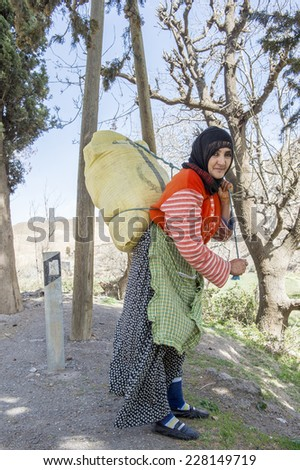 TISLDAY, MOROCCO, MARCH 10, 2014. An old woman with traditional Moroccan clothes and a black headscarf carrying a big bag in her back in Tislady, Morocco, on March 10th, 2014. - stock photo