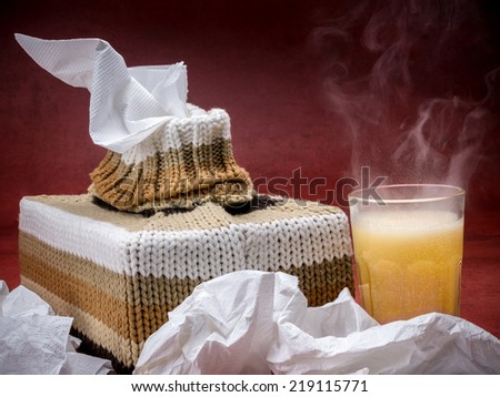 Tissue box in knit encasement and hot flu medicine drink over dark red background - stock photo
