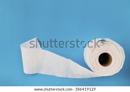 Tissue paper roll on the blue background. - stock photo