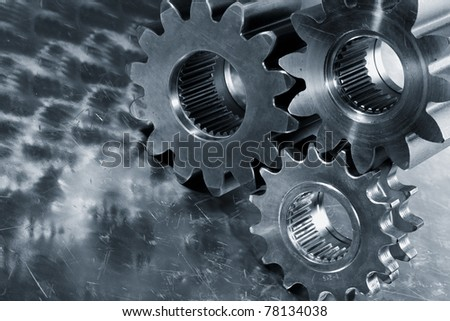 titanium and steel gears against brushed aluminum, bluish toning idea