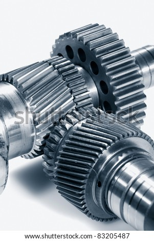 titanium and steel gears set against light background, ideal for isolations. - stock photo