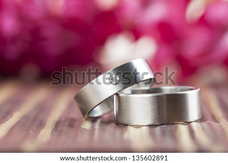 Titanium wedding rings with red hyacinth in the background. Shallow dof - stock photo
