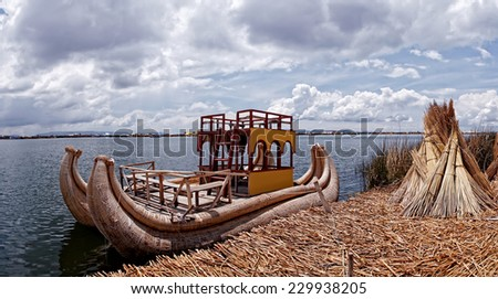Titicaca lake reed boat anchoring at the traditional reed islands of the Uru people - stock photo