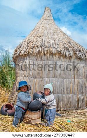 TITICACA, PERU, MARCH 19, 2015 -Children in traditional village on floating Uros  islands on lake Titicaca in Peru. - stock photo
