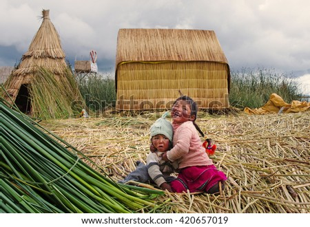 TITICACA, PERU, MARCH 19, 2015: Children in traditional village on floating Uros  islands on lake Titicaca in Peru, South America  - stock photo