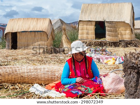TITICACA, PERU, MARCH 19, 2015: People in traditional village on floating Uros  islands on lake Titicaca in Peru, South America  - stock photo