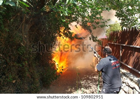 TIVON, ISRAEL - AUGUST 09: A man tries to save his home from burning after a forest fire breaks out in Kiryat Tivon. Rescue workers struggle to prevent further damage. Tivon, Israel August 09, 2012 - stock photo