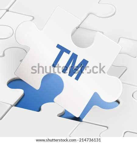 TM word on white puzzle pieces background - stock photo