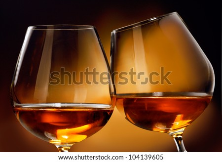 To clink two glasses of Cognac or Brandy liquor in front of a brownish background. - stock photo