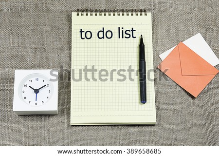 to do list on clipboard with a pen, desk clock and small letter envelope  notes against burlap canvas - office abstract - stock photo