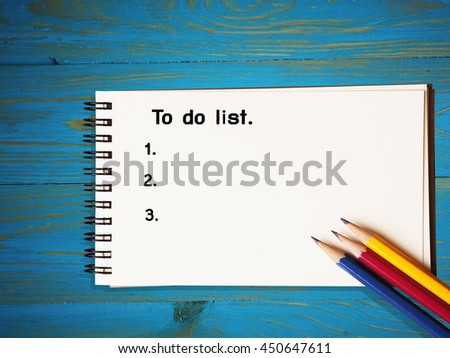 To do list on note paper on blue wood table background style.