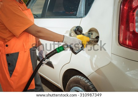 To fill the machine with fuel. car fill with gasoline at a gas station. Gas station pump. filling gasoline fuel in car holding nozzle. Close up. - stock photo