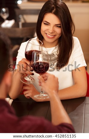To our future. Vertical portrait of a stunning brunette female enjoying her date at the restaurant smiling happily - stock photo