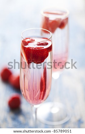 to refreshing strawberry champagne cocktails on a rustic garden table - stock photo