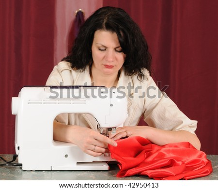 To sew a  material on the sewing machine - stock photo