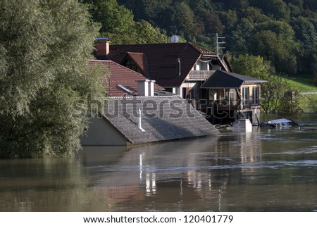 To the roof flooded house after heavy rain. - stock photo