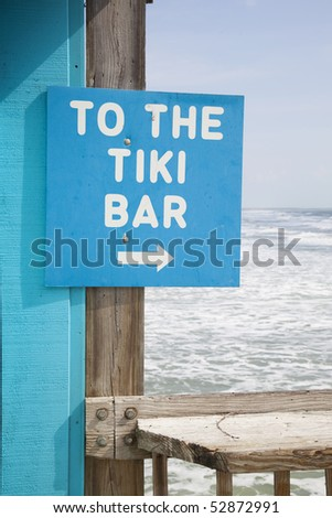 To the tiki bar sign with breaking waves in background. - stock photo