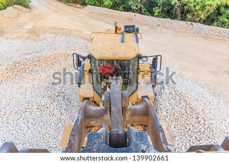 to view of wheel loader on the gravel pit - stock photo