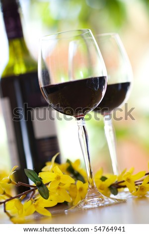 to wine glasses filled with red wine and wine bottle in background - stock photo