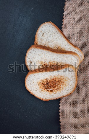 Toast baguette on slate. The toasted bread. The bread is white on a black background. Bread on wooden background - stock photo