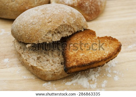 Toast bread cut in the shape of hearts being eaten by the bun, with nature wooden background and white flour. Concept about love. - stock photo