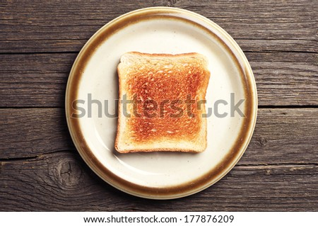 Toast bread in a brown plate on vintage wooden background. Top view - stock photo