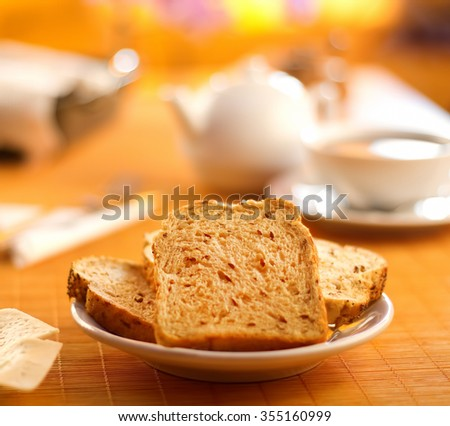 Toast bread on a plate with a cup of tea/coffee on breakfast table  - stock photo