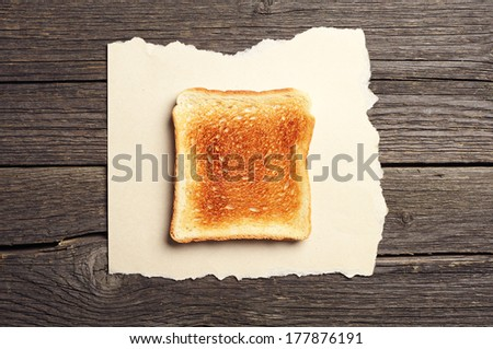 Toast bread on torn paper on vintage wooden background. Top view - stock photo