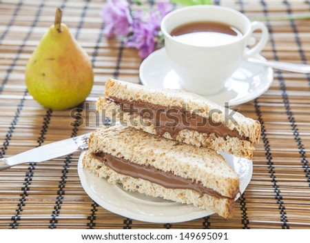 toast bread with creamy chocolate and tea, delicious breakfast - stock photo