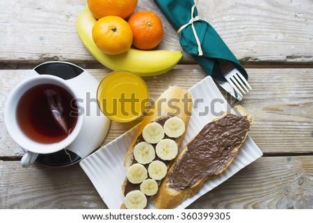 toast, chocolate spread with bread, tea, orange juice, fruit. healthy food, tasty concept. Banana toast sandwich with chocolate. selective focus, toned image - stock photo