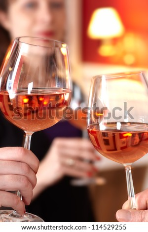 Toast in restaurant with full glasses of wine - celebration concept