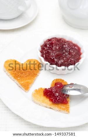 toast in the shape of hearts and berry jam, close-up - stock photo