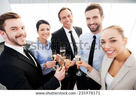Toast to success. Group of business people toasting with champagne and smiling while standing close to each - stock photo