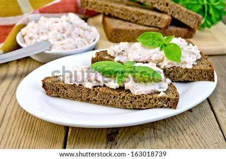 Toast two slices of rye bread with cream of salmon and mayonnaise, basil, knife, napkin, parsley on a wooden boards background - stock photo